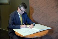 Księgę pamiątkową podpisuje Szef Służby Cywilnej