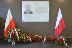 Kwiaty pod tablicą upamiętniającą Patrona KSAP