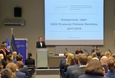 Przy mównicy przemawia Dyrektor KSAP. Zgromadzeni goście siedzą, po lewej widać poczet sztandarowy.