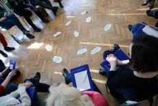 Na podłodze leżą karteczki w kształcie chmur. Uczestnicy warsztatu siedzą dookoła.
