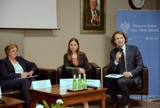 Prelegenci siedzą na fotelach , moderator rozmowy Marcin Sakowicz trzyma mikrofon i mówi do uczestników konferencji