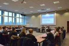 Studenici siedzą w sali przy ławkach. A przy prezydium siedzi Katarzyna Woś, Kierownik Biura Dyrektora, Dyrektor KSAP Jan Pastwa i Anna Budzikowska.