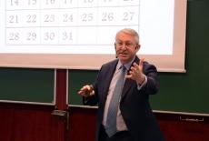 Wykładowca z mikrofonem nausznym gestykuluje i przemawia do uczesników