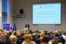 Uczestnicy seminarium w auli KSAP, Dyrektor KSAP przemawia przy mównicy, w tle na dużym ekranie wyświetlona prezentacja z tytułem i logo seminarium