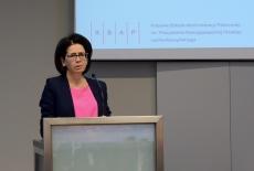 Minister Cyfryzacji przemawia przy mównicy, w tle wyświetlone loga KSAP