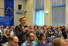 Uczestnicy spotkania w auli KSAP. Jedna uczestniczka zadaje pytanie. W tle baner KSAP i flaga UE.