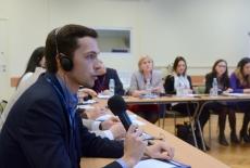 Uczestnik ze słuchawkami na uszach siedzi i mówi do mikrofonu