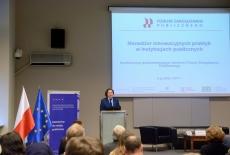 Przedstawiciel KSAP przy mównicy. W tle ekran z wyświetlonym tytułem konferencji, baner KSAP i flagi polska i unijna.