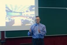 Wykładowca stoi przed uczestnikami gestykuluje i przemawia za nim wyświetlana jest prezentacja