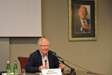 Maciej Wierzyński siedzi przy stole prezydialnym i prowadzi wykład.