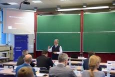 Wykładowca z nausznym mikrofonem stoi przy stole i przemawia do uczestników