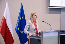 przy mównicy zastępca dyrektora KSAP, obok stoją flagi Polski i Unii Europejskiej