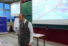 Wykładowca z nausznym mikrofonem stoi i przemawia