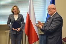 Na tle flag Polski i UE stoją: Iryna Vereshchuk - trzyma teczkę z certyfikatem i Dyrektor KSAP - klaszcze.