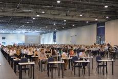 Uczestnicy egazminu siedzą przy stolikach w hali egazminacyjnej.