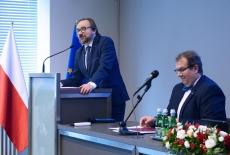 Przedstawiciel Prezesa Rady Ministrów przemawia przy mównicy, obok siedzi Dyrektor KSAP