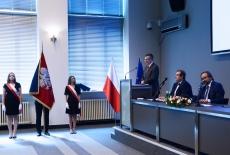 Za stołem prezydialnym siedzą trzy osoby, obok stoi poczet sztandarowy
