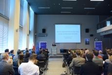 Uczestnicy konferencji w auli KSAP podczas wystąpienia prelegenta. Prelegent stoi przy mównicy. W tle na dużym ekranie wyświetlony tytuł konferencji.