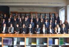 Zdjęcie grupowe słuchaczy XXVIII Promocji. Słuchacze stoją w bibliotece.
