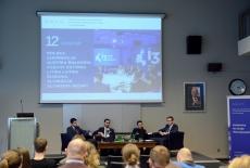 Czterech uczestników panelu siedzi na fotelach. Jeden mówi do mikrofonu. W tle na dużym ekranie wyświetlona prezentacja.