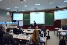 Uczestnicy szkolenia podczas zajęć w dużej sali wykładowej. W tle trzy ekrany z wyświetloną prezentacją.