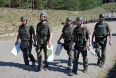 Słuchacze KSAP wracają ze strzelnicy. W rękach niosą papierowe tarcze.