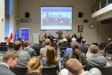 Uczestnicy spotkania w auli KSAP. Na ekranie wyświetlone duże zdjęcie grupowe absolwentów VI Promocji