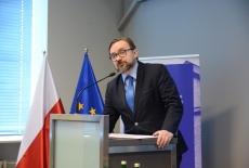 Wiceszef Kancelarii Prezesa Rady Ministrów przemawia przy mównicy. W tle flagi polska i unijna oraz baner KSAP