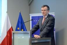 Szef Służby Cywilnej przemawia przy mównicy. W tle flagi polska i unijna oraz baner KSAP