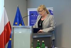 Posłanka Małgorzata Gosiewska przemawia przy mównicy. W tle flagi polska i unijna oraz baner KSAP
