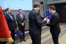 Dyrektor KSAP wręcza słuchaczowi dyplom. Obok stoją wiceszef KPRM i Szef Służby Cywilnej.
