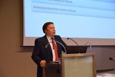 Grzegorz Kozłowski Dyrektor Dep. Ameryki MSZ wygłasza wykład stojąc przy mównicy.