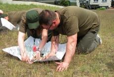 2 słuchaczy siedzi na trawie z rozłożoną przed nimi mapą i szukają odpowiednich szlaków