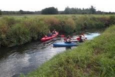Cztery osoby płyną w dwóch kajakach na rzece Rawce