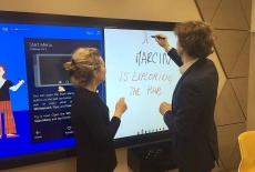 Dwóch uczestników spotkania stoi przy dużym ekranie zawieszonym na ścianie. Jeden z nich pisze na ekranie.