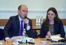 Dwójka uczestników szkolenia siedzi w ławce. Pan z lewej strony mówi przez mikrofon.