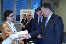 Uczestniczka szkolenia odbiera dyplom i podaje rękę przedstawicielowi MSZ.