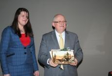 Dyrektor Jan Pastwa prezentuje prezent jaki dostał od przybyłych gości. Z lewej strony stoi pani z NAPA.