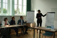 Wykładowca stoi i pokazuje na notatki na flipcharcie a uczestnicy siedzą