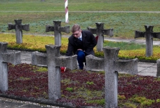 Słuchacz stawia znicz na cmentarzu w Palmirach