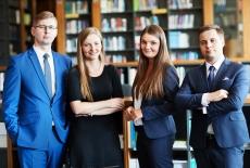 czterech młodych uśmiechniętych ludzi, w tle półki z książkami