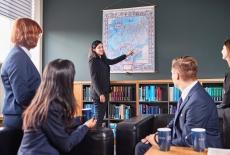 słuchacze KSAP siedzą na kanapach w bibliotece. Jedna słuchaczka stoi i pokazuje coś na mapie.