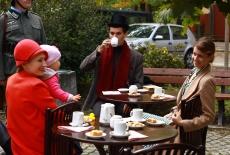 Uczestnicy gry, przebrani w stroje z lat trzydziestych, siedzą przy stoliku kawiarnianym.