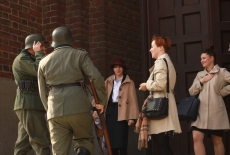 Uczestnicy przebrani za dwóch żołnierzy niemieckich oraz trzy kobiety w jasnych płaszczach.