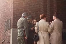 Uczestnicy przebrani za dwóch żołnierzy niemieckich oraz dwie kobiety w jasnych płaszczach.