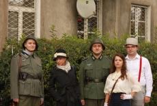 Uczestnicy gry - dwóch przebranych za niemieckich żołnierzy, dwie kobiety i jeden mężczyzna przebrani w stroje z epoki stoją przed kamienicą.