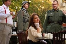 Jedna kobieta siedzi przy stoliku kawiarnianym, trzech mężczyzn stoi. Dwóch z nich przebranych jest za niemieckich żołnierzy.