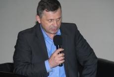 Uczestnik konferencji siedząc w fotelu mówi do mikrofonu.