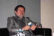 Zamyślony uczestnik konferencji, siedzi oparty o poręcz fotela.