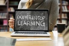 """na ekranie komputera czarna tablica z tekstem napisanym białą kredą """"(n) ever (s) top learning"""". Za komputerem siedzi kobieta"""